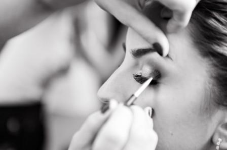 makeup artist applying eye shadow in black and white