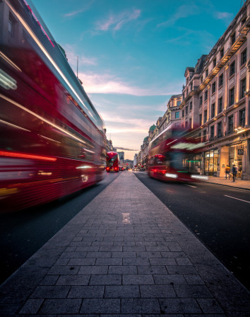 timelapse photography of double decker bus on road between buildings